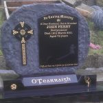 Boulder edged round headstone with polished celtic cross in black granite